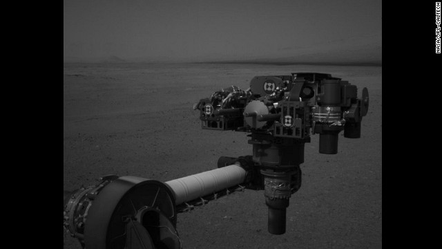 "Curiosity moved its robot arm on August 20, for the first time since it landed on Mars. ""It worked just as we planned,"" said JPL engineer Louise Jandura in a NASA press release. This picture shows the 7-foot-long arm holding a camera, a drill, a spectrometer, a scoop and other tools. The arm will undergo weeks of tests before it starts digging."