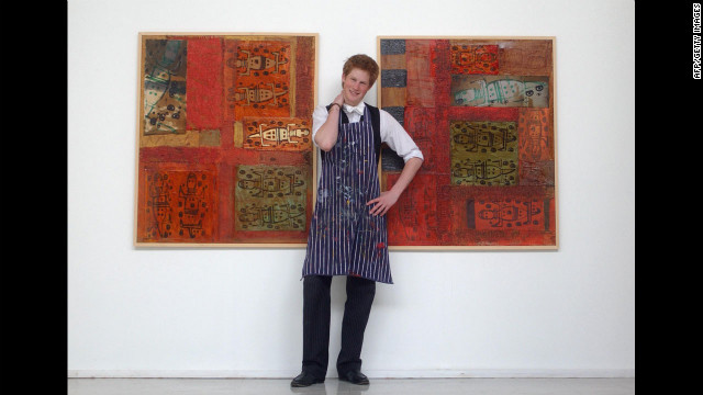 Prince Harry stands in the Drawing School on May 12, 2003, between two of the works he completed while studying at Eton College. His work involves a mixture of painting and printing, and reflects his habit of using animals as his starting point.