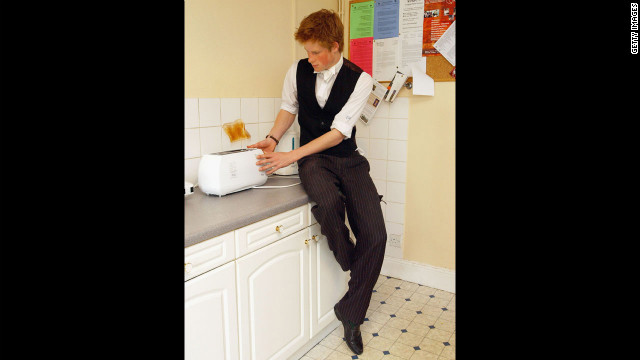 The youngest son of the Prince of Wales, Prince Harry makes a slice of toast in his house kitchen situated in the house library, which is the preserve of the senior House prefects, in March 2003 at Eton College.