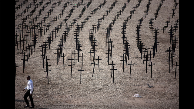 A man walks by crosses set up as memorials to the tens of thousands killed and buried in the mass grave at Titanyen on the outskirts of Port-au-Prince.