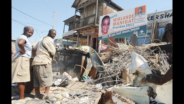 Earthquake debris in front of a campaign billboard for presidential candidate and former first lady Mirlande Manigat on March 19, 2011.