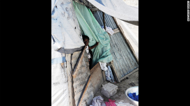 A young child looks out of one of the remaining tents in the St. Therese suburb of Port-au-Prince on July 5.
