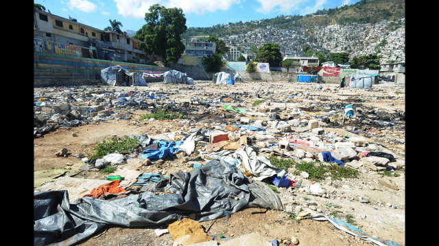 Trash and debris litter a field where once stood tents for surviviors of the earthquake.