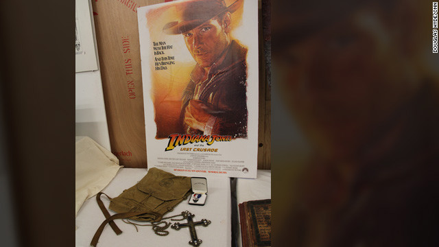 "Props from the opening sequence of ""Indiana Jones and the Last Crusade"" -- young Indy's Boy Scout backpack, Eagle Scout ribbon and the Spanish crucifix he encounters (""It belongs in a museum!!"")"