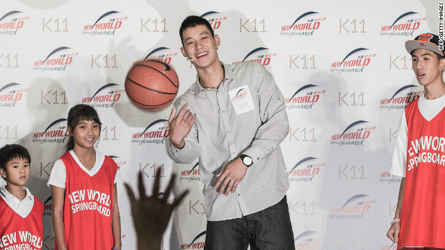 Jeremy Lin tosses a basketball during a promotional event in Hong Kong.
