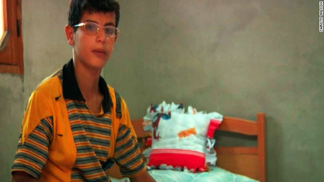 Jihad Mansour sits on his Spiderman bed in the room he used to share with his brother, who was killed on his way to school.
