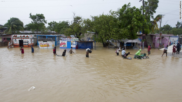 Residents leave their flooded homes with their possessions.