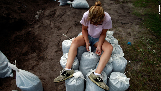 A woman sits atop sandbags filled by Tampa area residents in preparation for the storm.