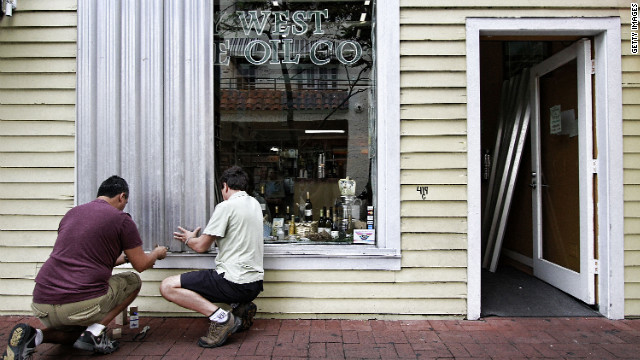 Two men install storm shutters on Duval Street on Saturday.