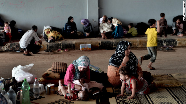 Displaced Syrian familes sit in a shelter at the border with Turkey after fleeing their homes from violence.