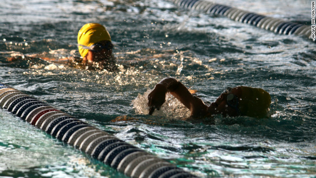 A junior takes a big breath before diving back into the water.
