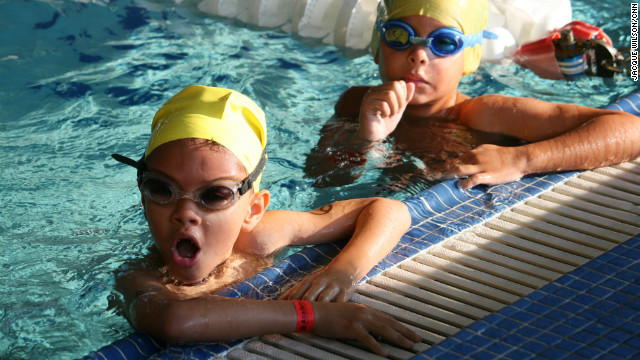 Two junior participants take a mini-break halfway through their swim portion. 