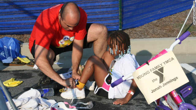 Jonah Jennings gets help from a race volunteer as she puts her sneakers on after the swim.