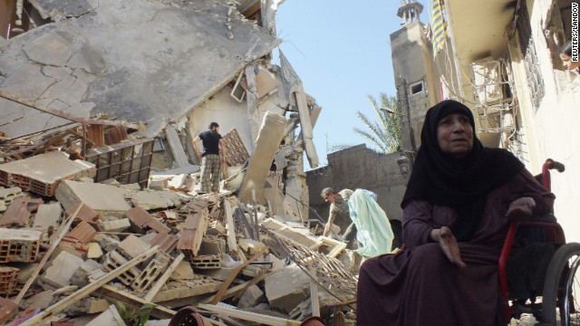 A woman sits in her wheelchair next to her house, damaged by a Syrian air raid, near Homs on August 26, 2012.