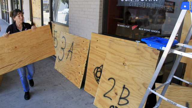 The manager of a shoe store in Harvey, Louisiana, places plywood over the windows in preparation of Hurricane Isaac.