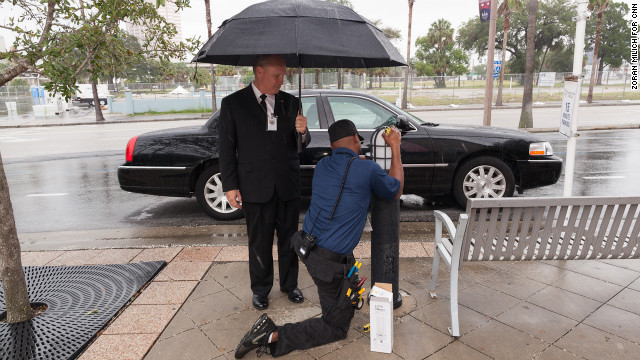 An electrician at the Tampa Bay Times Forum fixes a light as a limo driver awaits Republican delegates.