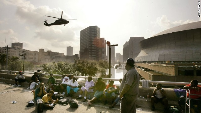 People seek high ground on the I-90 Freeway as a helicopter prepares to land at the Supedome on August 31, 2005, in New Orleans.