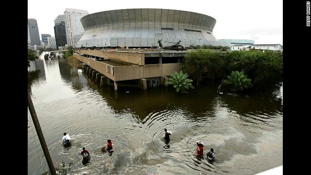 People walk through high water in front of the Superdome.