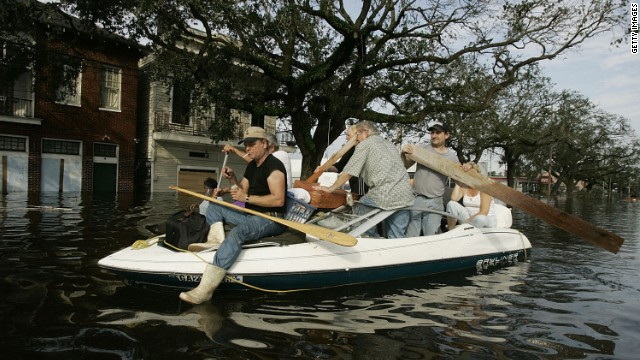 People use a boat to get to higher ground as water began to rise in the area on August 30, 2005, in New Orleans.
