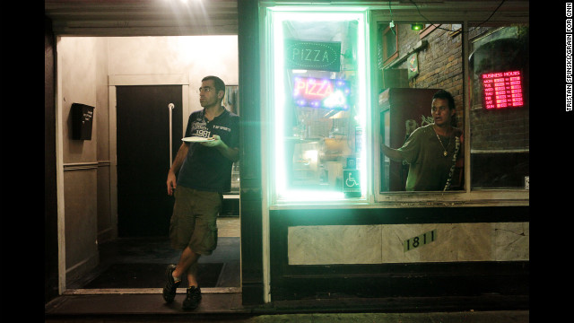 Pizza parlor patrons watch the anti-Romney protest march.