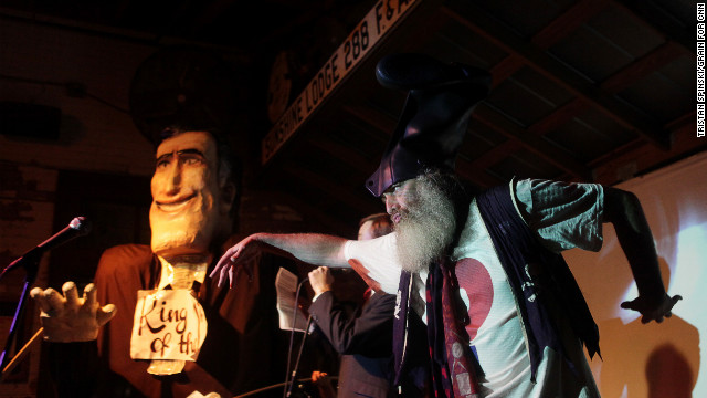 """Ritt Momney"" engages in a mock political debate with Vermin Supreme, right, a performance artist and activist."