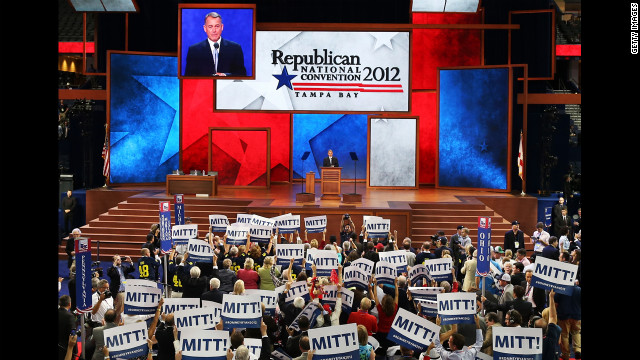 People hold signs that say &quot;Mitt!&quot; as U.S. Speaker of the House Rep. John Boehner, R-Ohio, speaks.
