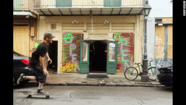A man skateboards past a bar with boarded windows in the French Quarter in New Orleans.