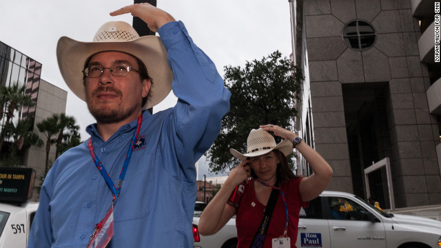 Texas delegates Jason Kute and Stephanie Traska hang on to their hats in the windy Florida city.