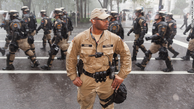 Riot police walk through the rainy streets of Tampa on Monday.