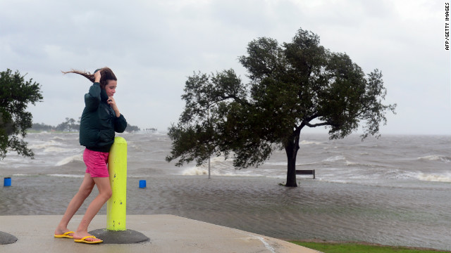 Emily Schneider leans against a pole to support herself against strong winds while visiting the banks of Lake Pontchartrain in New Orleans, where Hurricane Isaac has made landfall.