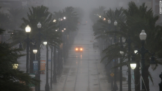 A car drives down Canal Street on Wednesday. The storm is slowly moving across southeast Louisiana, dumping large amounts of rain and knocking out power in scattered parts of the state.