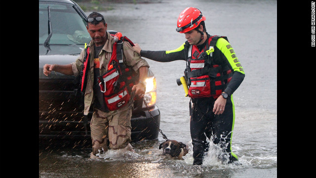 John Stone of Bay St. Louis, Mississippi, and his dog are led out of the water by a member of the Swift Water Rescue Team after being rescued from his flooded house.