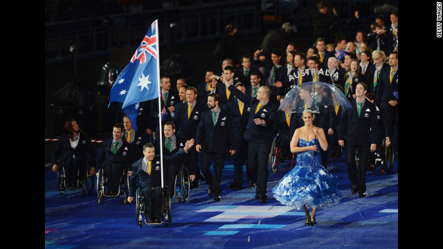 Wheelchair rugby player Greg Smith of Australia carries the flag during the ceremony.