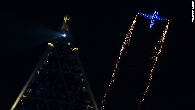 A small plane trails sparks over the Olympic Stadium.