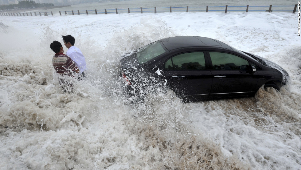 Men wait for help by a stranded car on a seaside road, surrounded by waves whipped up by typhoon Bolaven in Qingdao, Shandong province, on Wednesday, August 28. Gales and downpours brought by typhoon Bolaven swept through parts of northeast China from Tuesday evening to Wednesday, flooding cities and delaying flights, Xinhua News Agency reported. 