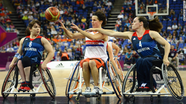 The Netherlands' Inge Huitzing passes the ball as Britain's Laurie Williams, left, and Caroline Maclean defend during the preliminary women's group A wheelchair basketball match.