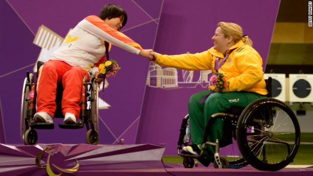 Cuiping Zhang, left, of China and Natalie Smith, right, of Australia shake hands on the podium after the women's R2 10-meter air rifle standing SH1 final.