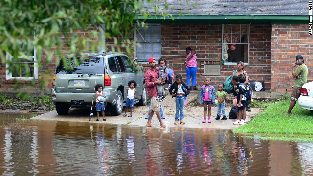 Residents stand in front of their home as flooded streets engulf their neighborhood in Slidell.