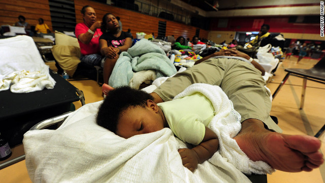 A child and an adult share a folding bed as storm-weary residents take refuge at a high school gymnasium in Belle Chasse, in low-lying Plaquemines Parish, outside of New Orleans.