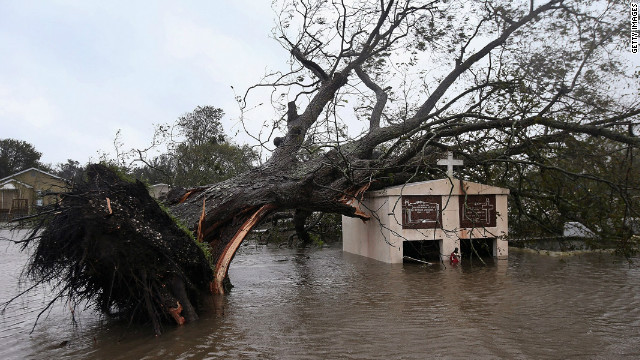 A tree blown over from Hurricane Isaac lies atop a cemetery tomb in Plaquemines Parish.