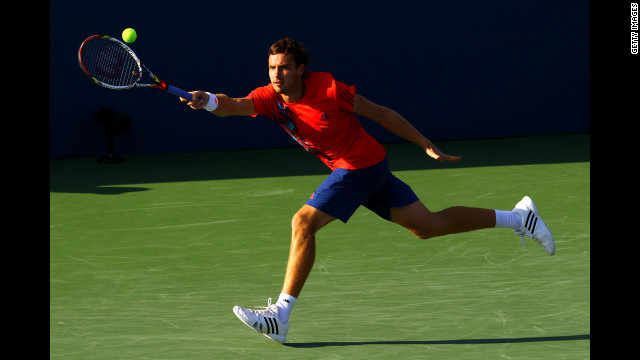 Latvian Ernests Gulbis stretches for the fall during his men's singles first-round match against German Tommy Haas.