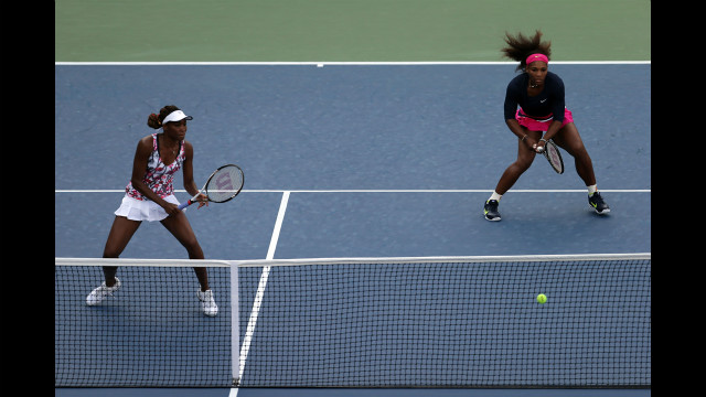 Sisters and doubles partners Venus Williams, left, and Serena Williams of the U.S. take on U.S. players Mallory Burdette and Nicole Gibbs during their women's doubles first-round match.