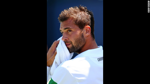 Benoit Paire of France wipes his face during his men's singles first-round match against Bulgarian Grigor Dimitrov.