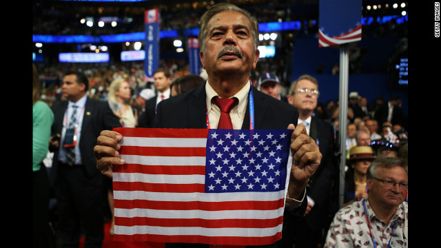A man holds an American flag in the audience.