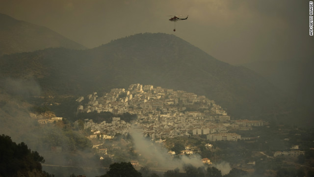 A fire brigade helicopter prepares to pour water to extinguish a wildfire in the village of Ojen on August 31, 2012. Some 4,000 people have been evacuated from the area with an additional 2,000 evacuated from the eastern part of Marbella.