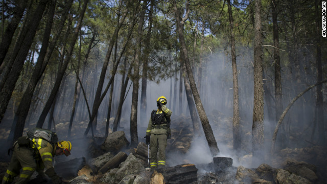 Firefighters try to extinguish a wildfire in Robledo de Chavela, 60kms west of Madrid, on August 28, 2012. Some 2,000 people who were evacuated due to raging wildfires in the west of Madrid were allowed to return to their homes three days later.