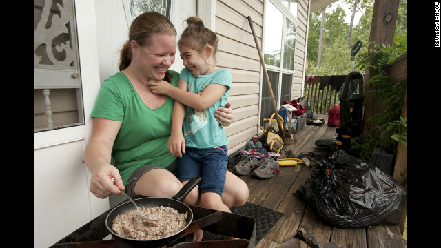 Vivian Lane, 5, helps her mother, Ashley Lane, make rice and gravy on their porch after Hurricane Isaac knocked out their power in Bay Saint Louis, Mississippi, Friday.