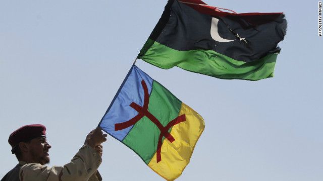 A soldier waves Libyan and Amazigh flags on the frontline of battle against the remnants of the Gadhafi regime in September 2011. The red symbol on the Amazigh flag is the character for &quot;free man,&quot; the name by which Berbers to themselves in Tamazight.