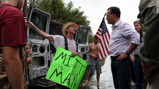 Republican presidential candidate Mitt Romney talks with a man on the side of the road while on an unscheduled tour of a neighorhood damaged by Isaac on Friday, August 31, in Lafitte, Louisiana.