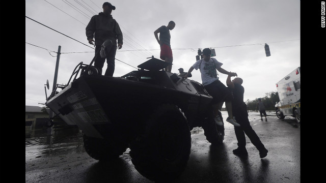 People get off a Slidell Police Department SWAT vehicle after being rescued from flooding from Isaac's storm surge on the north shore of Lake Pontchartrain.